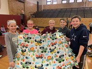 BCIS students showing animal blanket made for Akron Children's Hospital