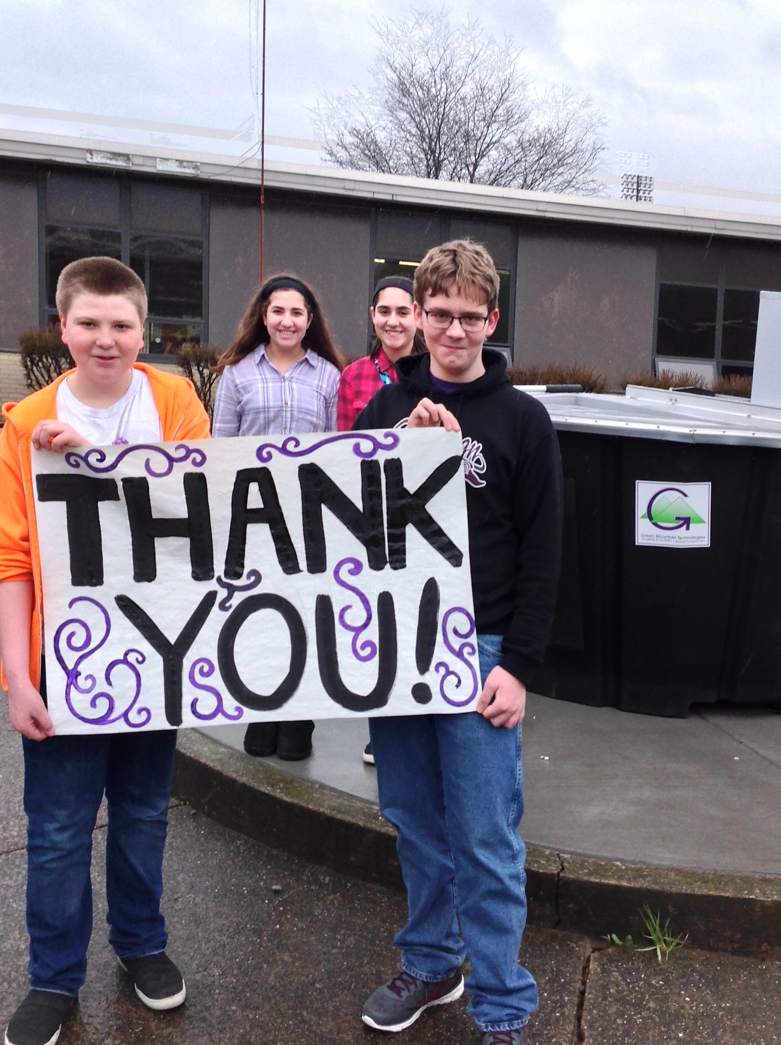 students with thank you sign in front of composter
