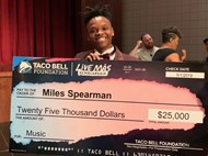 Miles holds his 25,000 dollar check from the Taco Bell Foundation