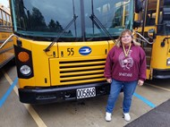 Laurie Woolley in front of bus number 55