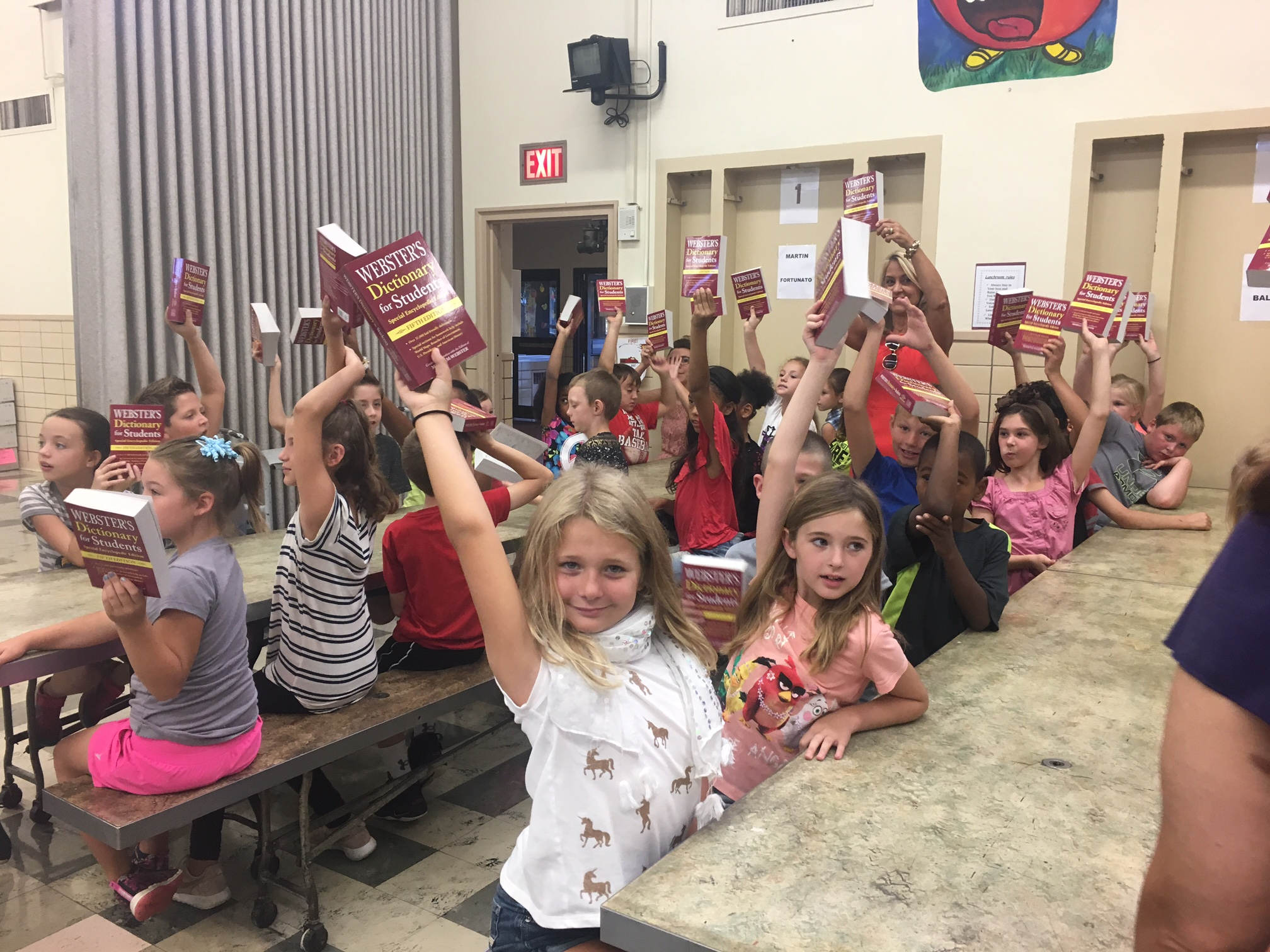 dictionary distribution kids holding books in air