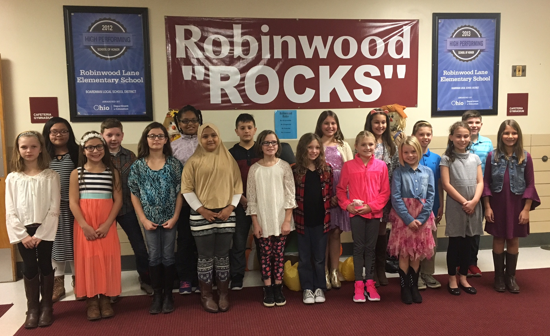 Writers Workshop students stand in front of school banner