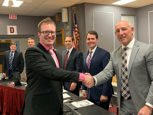 New transportation director, Ryan Dunn shakes hands with Supt. Tim Saxton