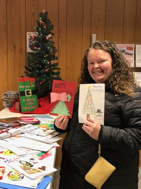Morgan Brandt holds cards for stockings for soldiers project