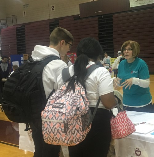Students carrying backpacks between classes to visit event in gymnasium