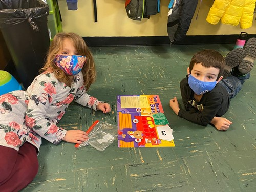 kindergarten students math work on classroom floor