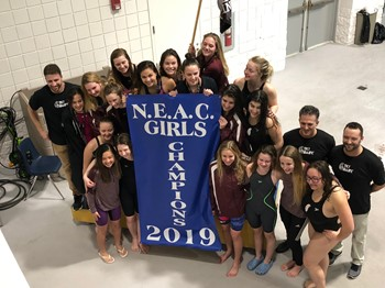 Girls Team at NEAC with banner poolside