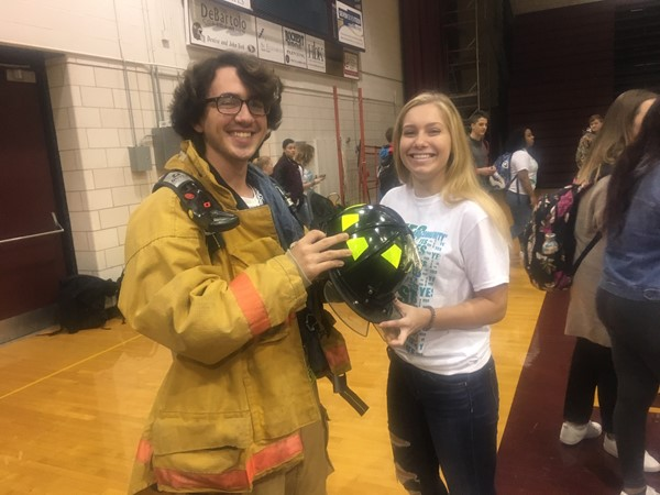 Senior Joe M. tries on Fire Department gear with the help of Volunteer Alyssa B.