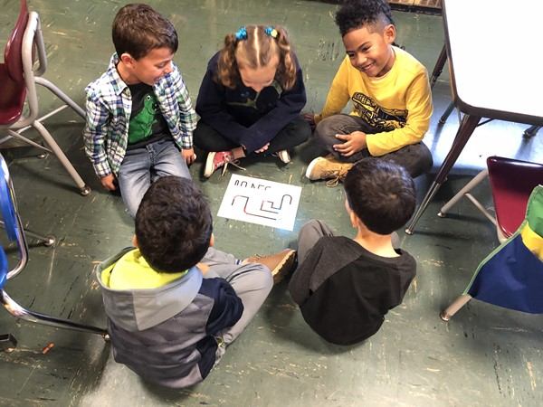 Students gather around and watch as the Ozobot slides across the floor.