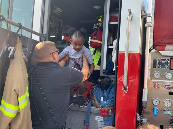 Firefighter helping child down from front seat of the firetruck