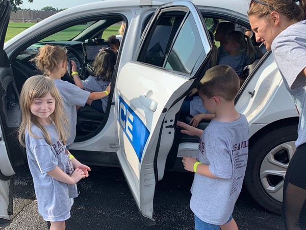 Kindergartners sitting inside police cruiser