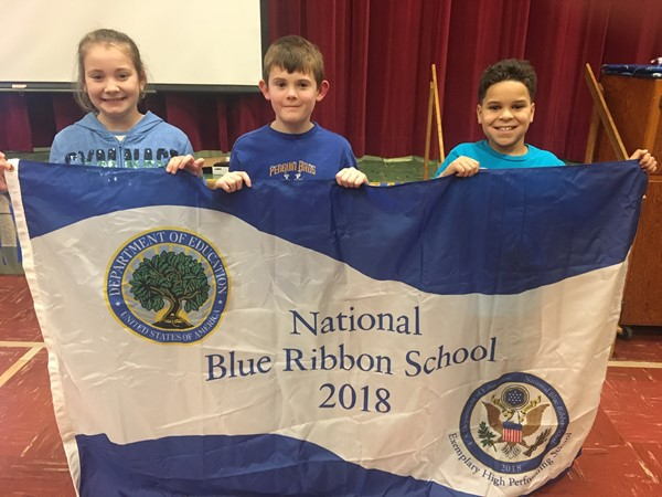 4th graders Ally, Jessen, and Antonio hold the Blue Ribbon schools banner for assembly.