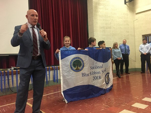 Mr. Saxton talks with students for all school rally to accept banner and blue ribbon award.