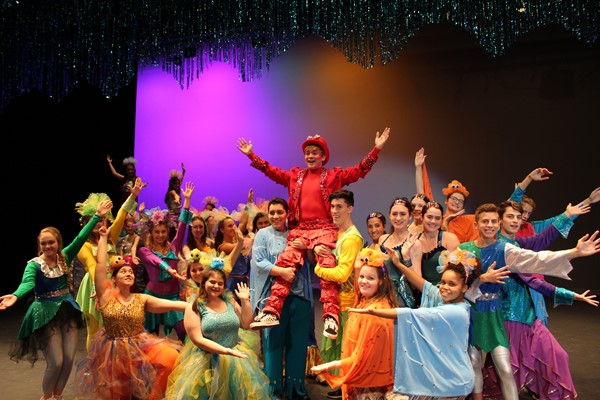 Cast of The Little Mermaid holding up Sebastian, played by Daniel Gordiejew