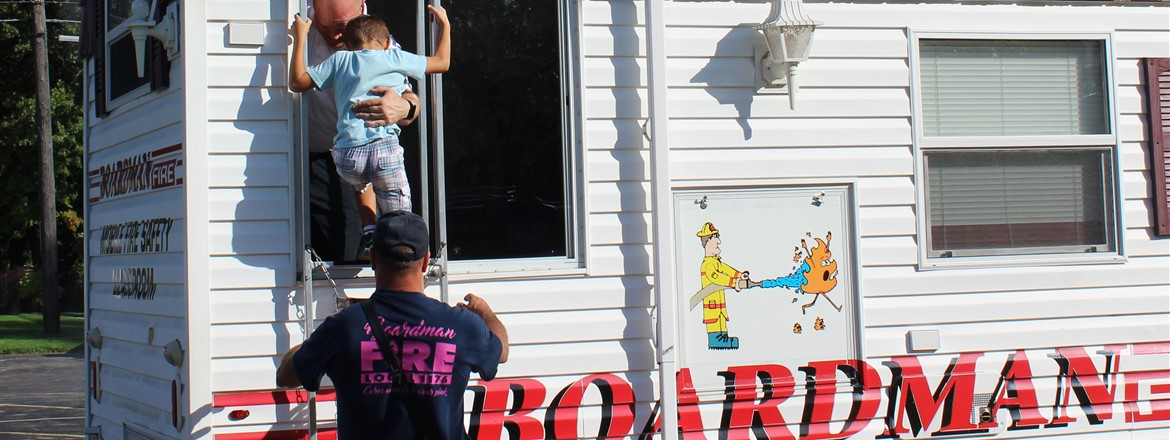 student being helped exit a window from the smokehouse mobile classroom