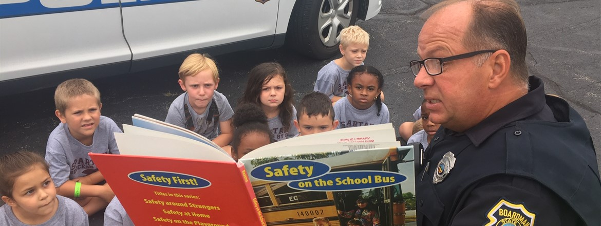 students listenting to officer Salser reading about bus safety outside as part of safety village