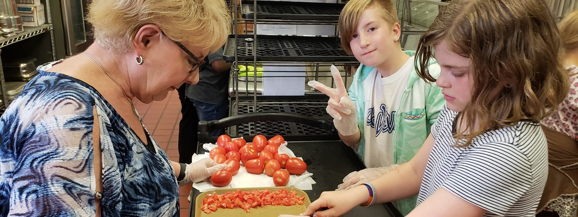 Students chopping tomatoes to make salsa from their Sprouting Spartans Gardening Club