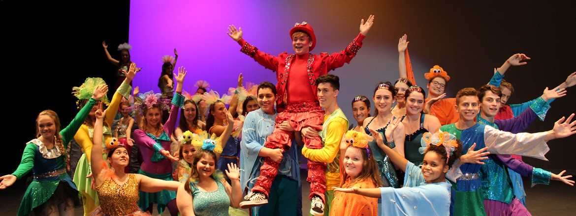 "Cast of the Little Mermaid lifting ""Sebastian"" up during performance on stage."