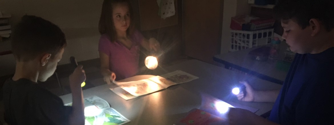 Three students using flashlights to read picture books  to each other