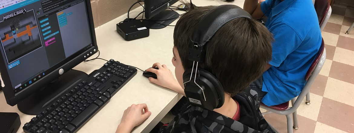 boy at computer with minecraft on screen as part of coding lesson