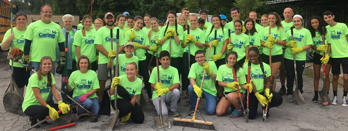 More than 40 students and staff members dressed in bright green Day of Caring shirts with landscaping tools, shovels, and brooms take group photo before neighborhood cleanup