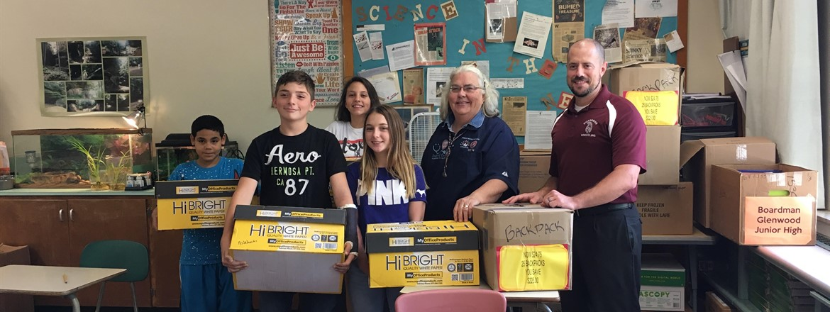 Students holding boxes full of school supplies with Mission of Love organizer and Science teacher  Eric Diefenderfer