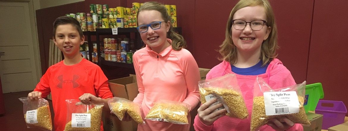 Students holding bags of split peas in the BCIS food pantry