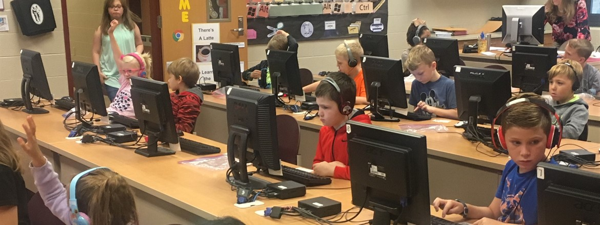 Students with headphones on in computer lab, working on keyboarding skills