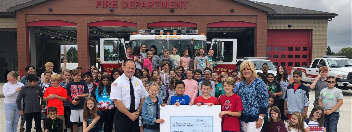 about 50 Students present check for Emergency Services Memorial standing in front of Fire Station 71 with Fire Chief Pitzer.