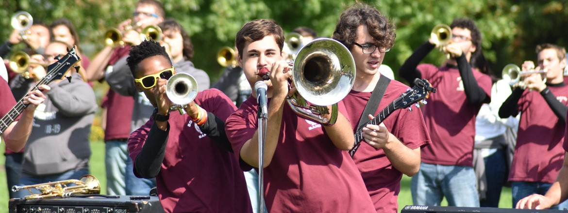 3 students in front of microphone , trumpet, electric guitar, and trombone with band playing behind during band camp