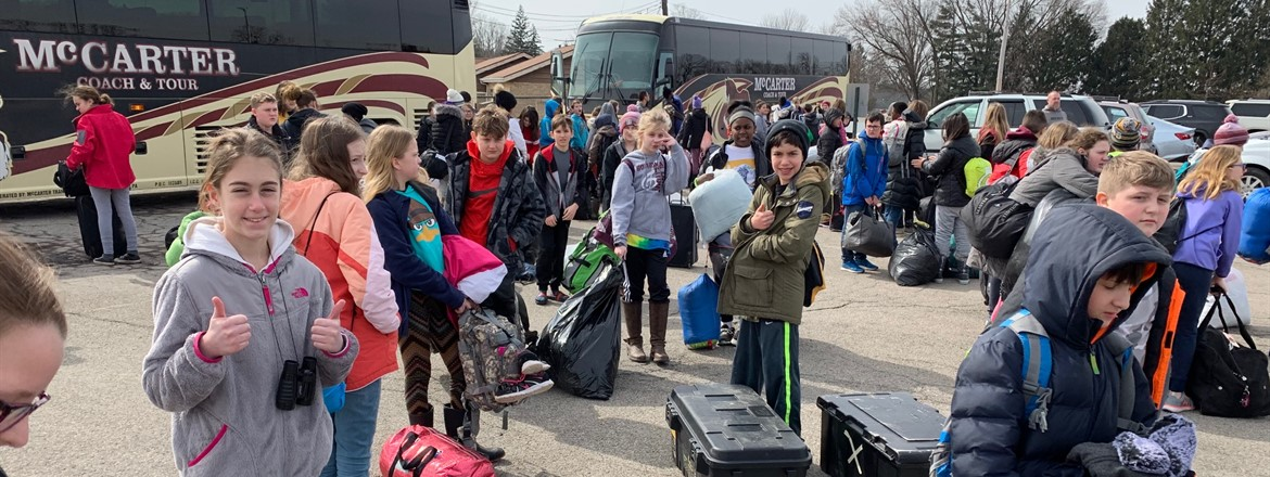 students with luggage in front of buses just home from Camp Fitch