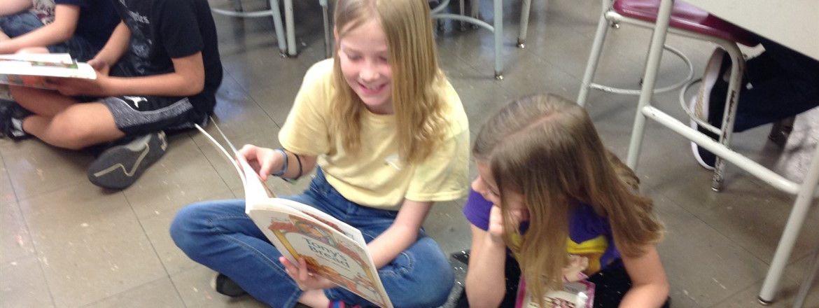 Girls reading out loud together sitting on the floor in the classroom for Right to Read week.