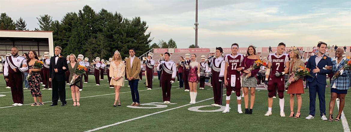 Homecoming court with escorts and marching band on football field