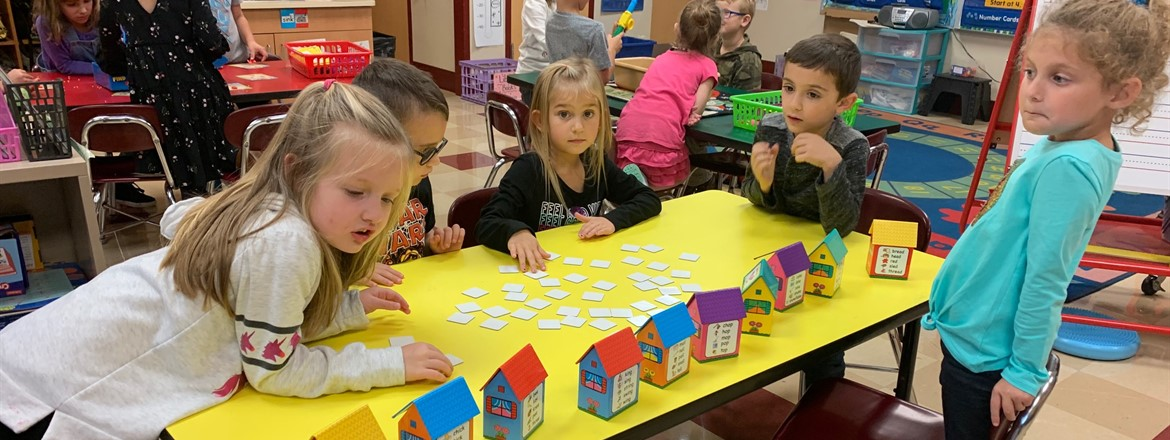 students using game with cardboard houses and rhyming words