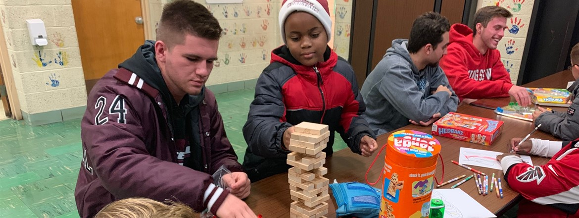 High school students playing jenga and trouble with stadium drive students as part of mentoring  program