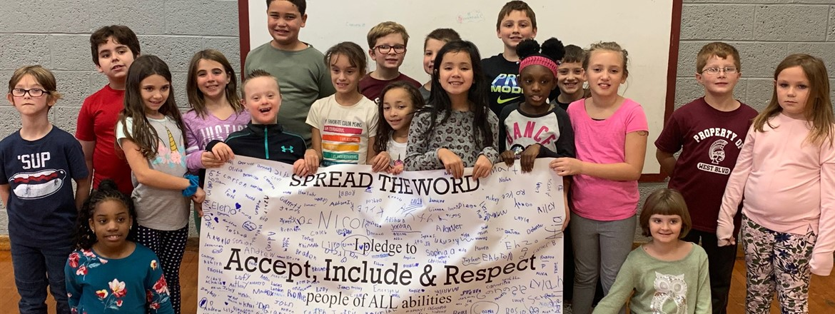 3rd grade students holding spread the word banner to accept, include, and resppect people of All abilities.