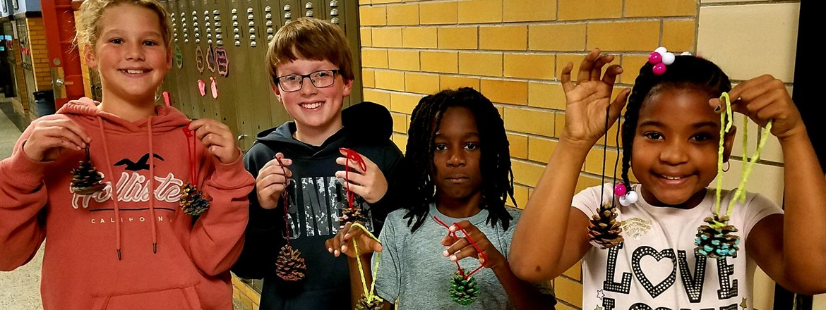 students holding up pine cone ornaments they made to send to soldiers overseas