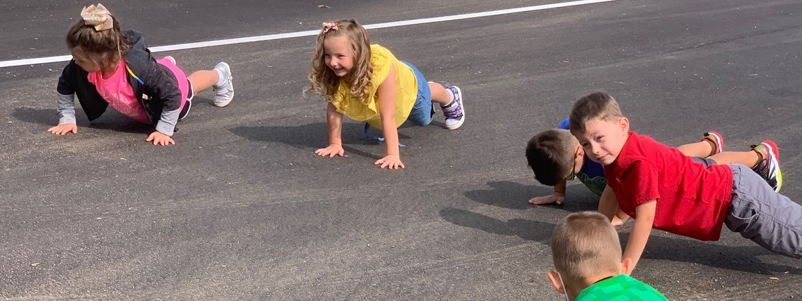 first graders doing push ups outside near the playground