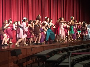 women's chorale dressed in Disney theme sing on stage