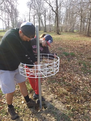 Mr. Shevock and daughter constructing disc gof basket