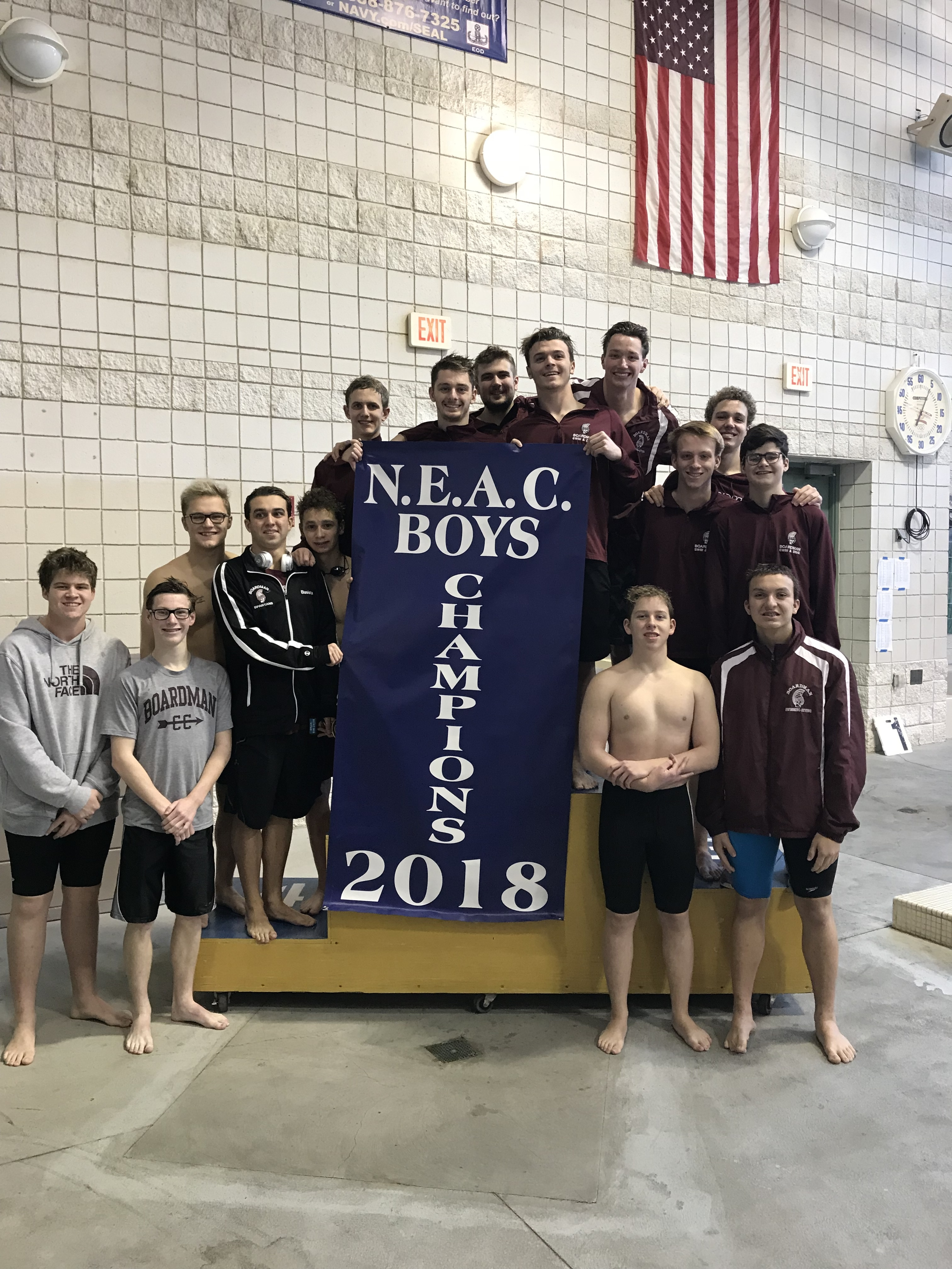 boys swim and dive team pose with NEAC championship banner poolside