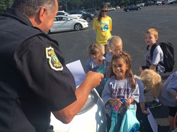 little girl smiling at police officer