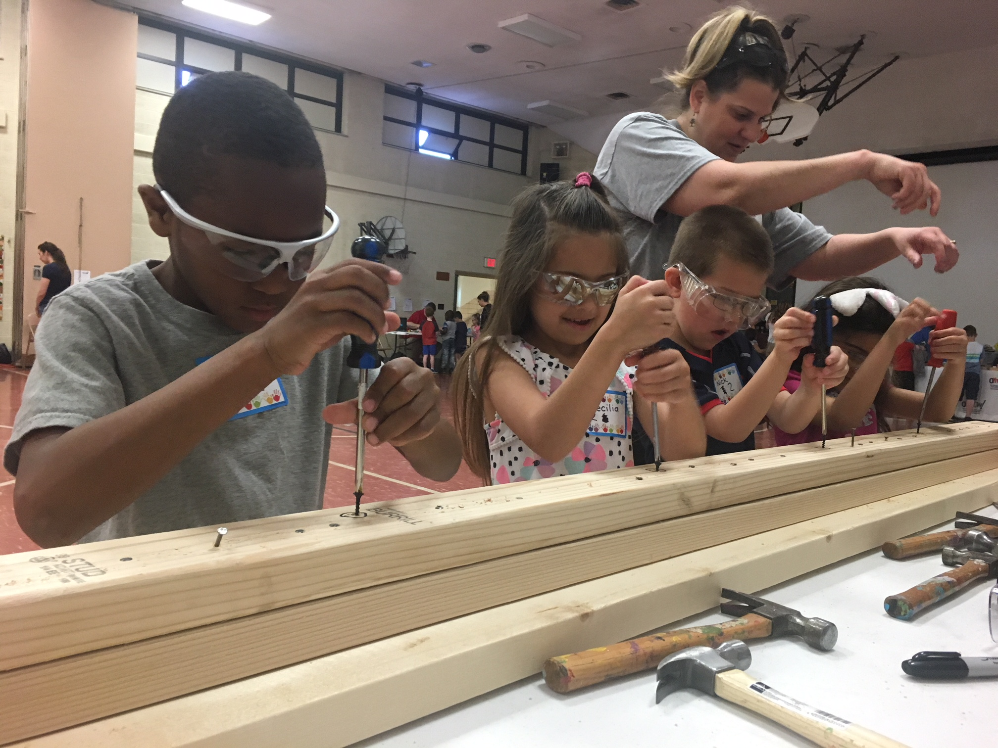 STEM event students  using screw drivers and other woodworking tools