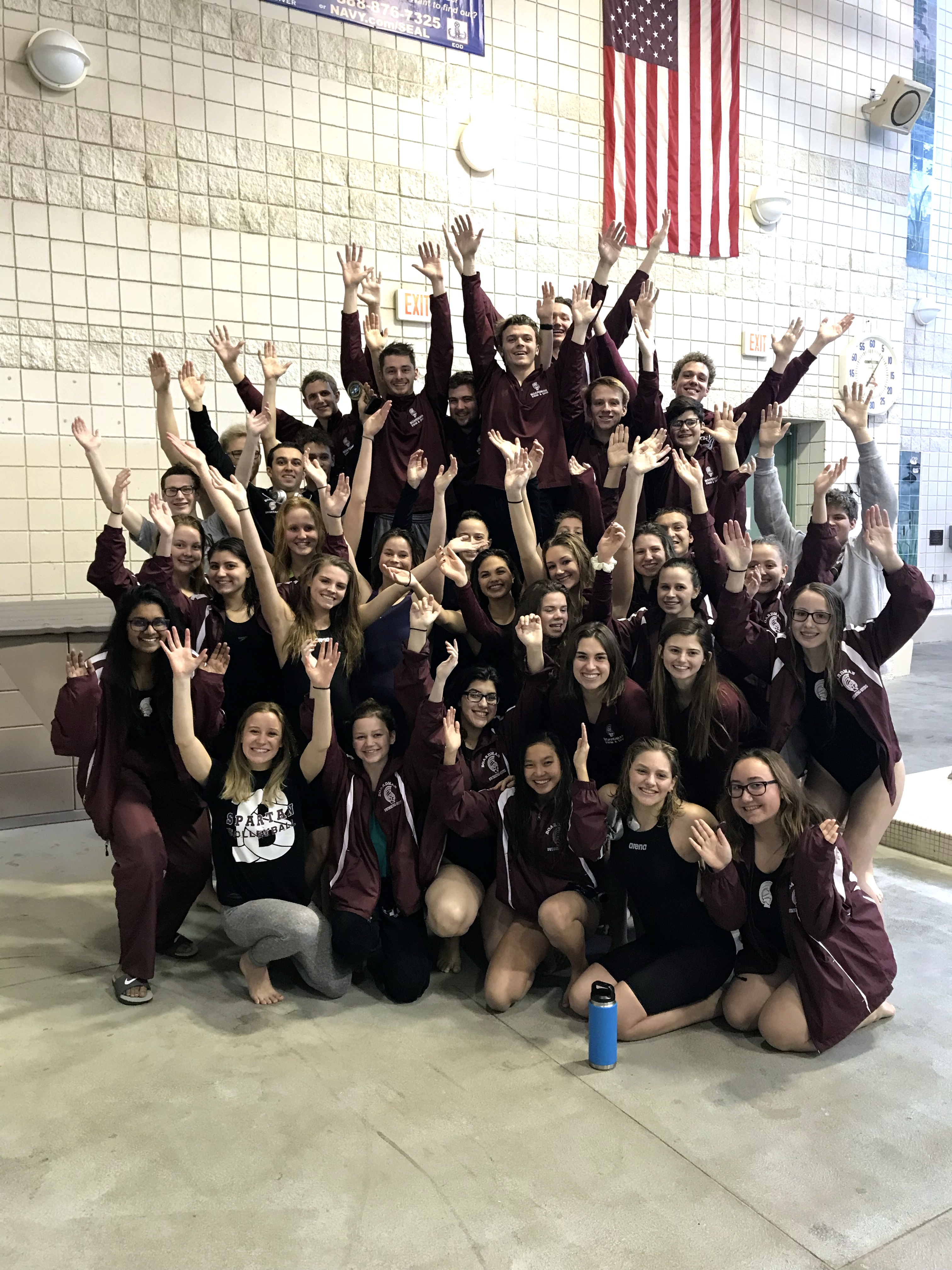 Boys and Girls Swim and Dive Teams with hands in air