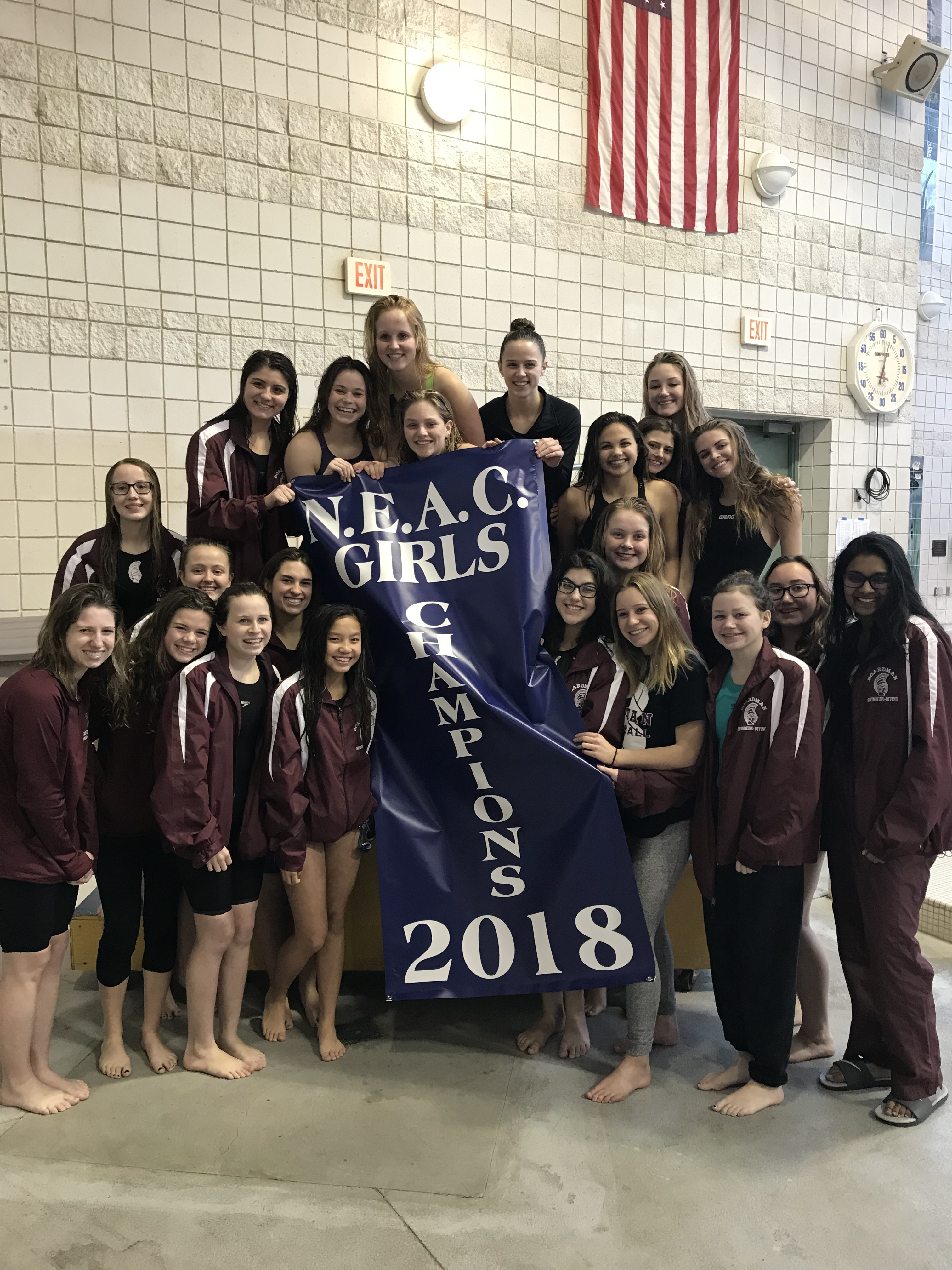 girls swim and dive team pose with NEAC championship banner poolside