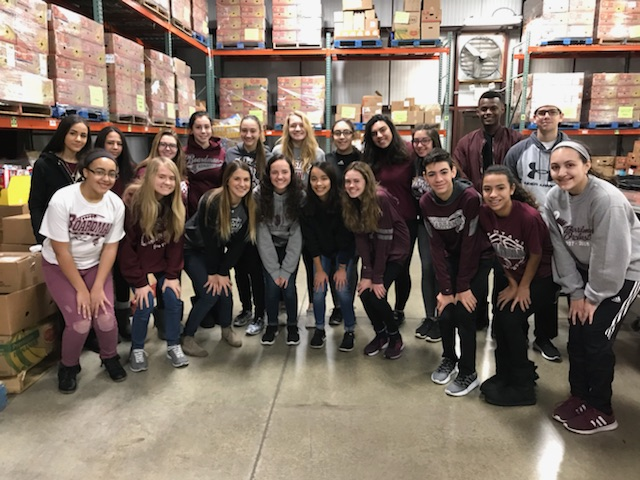 group picture of 20 students inside the Second Harvest warehouse